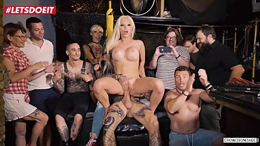 Tattooed blonde in BDSM scene at a party